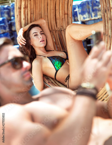 Photo sur Toile Artiste KB Young, attractive couple relaxing on a tropical beach