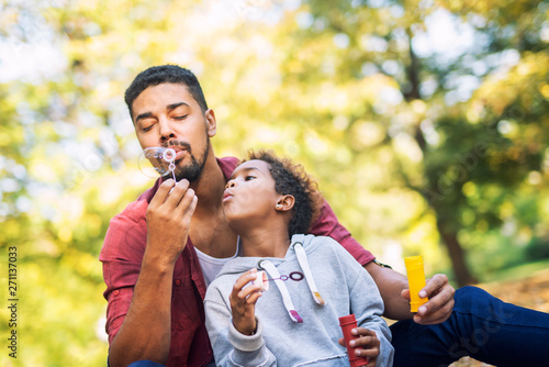 Photo sur Toile Kiev Father and daughter blowing soap bubbles enjoying together. Afro American family time. Happy girl watching her daddy making balloons.