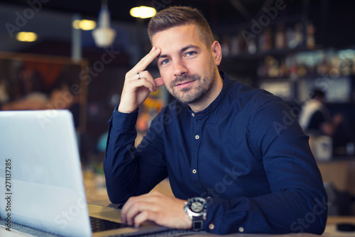 Fotografía  Young caucasian businessman siting at cafeteria with laptop computer on the table