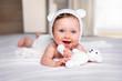 canvas print picture - Portrait eines glücklichen, süßen Baby Mädchens mit blauen Augen und Bärenmütze auf einem weißem Bett mit Stoff Bär