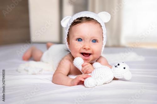 Photo sur Toile Les Textures Portrait eines glücklichen, süßen Baby Mädchens mit blauen Augen und Bärenmütze auf einem weißem Bett mit Stoff Bär