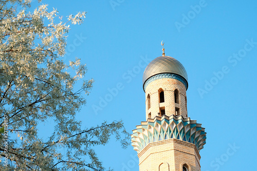 Papel de parede The Golden minaret of the mosque next to the green trees