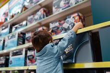 Little Boy At The Shelf In Kid...