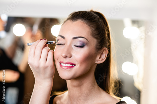 Photo sur Toile Les Textures Make up artist doing professional make up on beautiful young woman
