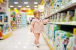 Leinwandbild Motiv Little girl choosing toys in kids store