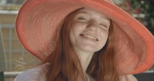 Portrait Of A Young Beautiful Red-haired Girl In A Wide Red Hat. The Girl Looks Very Happy And Fun On A Sunny Day. Real Time. Shot On Canon 1DX Mark2 4K Camera