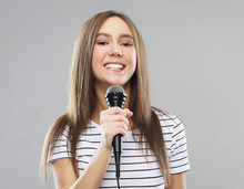 Beauty Model Girl Singer With A Microphone Over Light Grey  Background