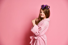 Pretty Young Lady Little Princess Teen Girl With Curlers In Her Hairs And In Bathrobe Stands At Free Text Space And Smiles Nicely On Pink