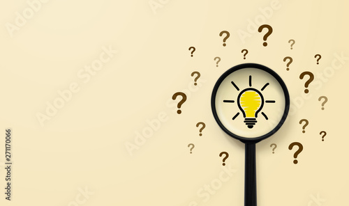 Fotografía Magnifying glass with light bulb icon and question mark symbol