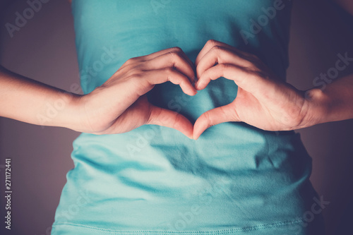 Fotografia  Woman hands making a heart shape on her stomach, healthy bowel degestion, probio