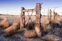 Wooden Fence With Barbed Wire On Old Route 66 In Valencia County, New Mexico At Sunset.