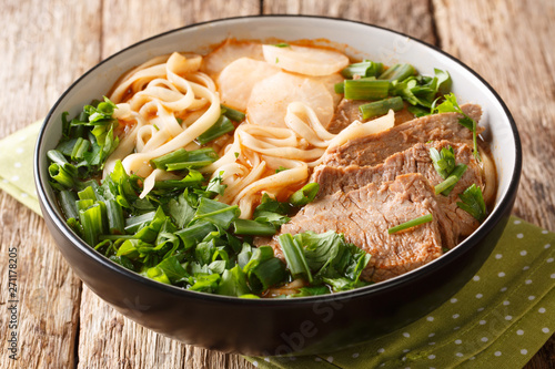 Lanzhou beef noodle soupis a type of Chinese ramen noodle soup with beef slices served on the top closeup in a bowl. horizontal