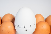 Chicken Eggs In The Package And White Timer On A White Background. Shelf Life. Time And Conditions Of Storage Of Eggs. To Boil Eggs.