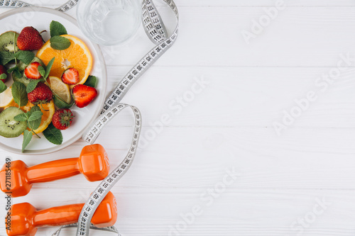 Photo  Diet plan, menu or program, tape measure, water, dumbbells and diet food of fres