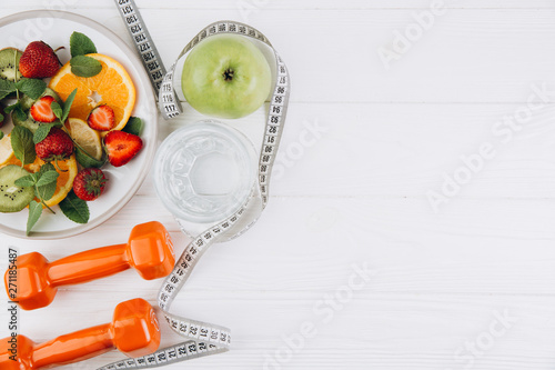 Foto Diet plan, menu or program, tape measure, water, dumbbells and diet food of fres