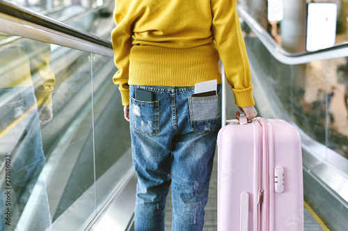 obraz dibond Traveller standing with a luggage at airport terminal, Passenger using escalator to departure check-in counter, Tourist arrive at destination, Travel concept.