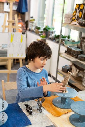 Poster Ecole de Danse Talented schoolboy sculpting clay figures in art school