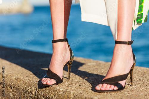 Fotografia  Woman feet in high heels shoes on sea pier