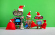canvas print picture - Happy 2020 New Year Merry Christmas robotic greeting card. Three funny Santa Claus robots with red bags of gifts, Xmas pine tree toy on green wall background.