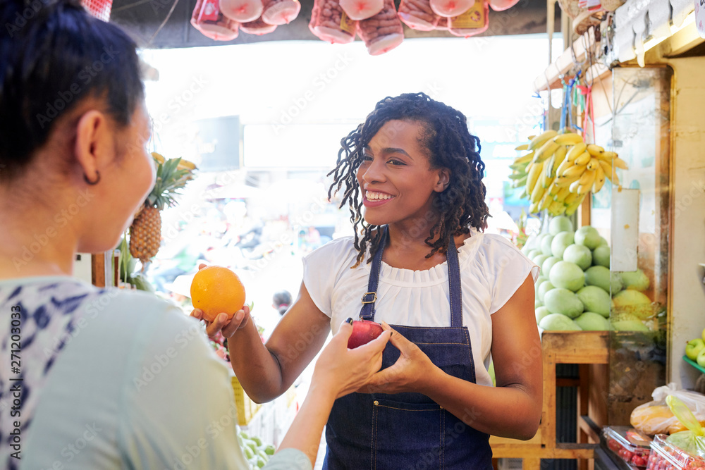 Fototapety, obrazy: Smiling pretty female fruit vendor helping customer with choosing best fruits