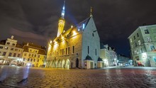 Night Motion Blur Time Lapse Of A Pedestrians Walking In A Square Showing The Colorful Houses And Restaurants In The Medieval City Of Tallinn With Moving Clouds In Estonia