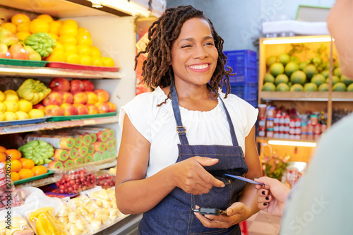 Cuadros en Lienzo Smiling pretty young grocery store worker with card reader talking to customer