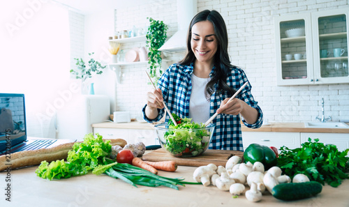 Obraz Beautiful young woman is preparing vegetable salad in the kitchen. Healthy Food. Vegan Salad. Diet. Dieting Concept. Healthy Lifestyle. Cooking At Home. Prepare Food. Cutting ingredients on table - fototapety do salonu