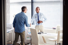 Mature Male Patient Shaking Hands With Doctor In Office