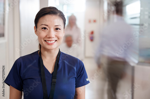 Fototapeta  Portrait Of Smiling Female Nurse Wearing Scrubs In Busy Hospital Corridor