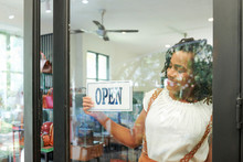 Smiling Female Shop Assistant Turning Sign On The Door When Opening Store