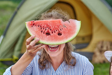 Funny Woman Eating Watermelon On A Picnic. Girl Closed Her Eyes With A Watermelon, Looking Into The Holes