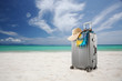 Leinwandbild Motiv View of gray suitcase with pareo and hat on tropical  beach