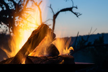 The Flames Of A Campfire At Dusk On Safari In Africa, Hluhluwe-iMfolozi, South Africa.