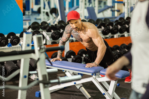 fototapeta na drzwi i meble Strong sporty man doing push-ups on bench during workout in gym