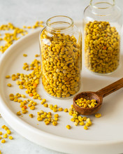 Bee Pollen In Glass Vial And Wooden Spoon On White Stone Background