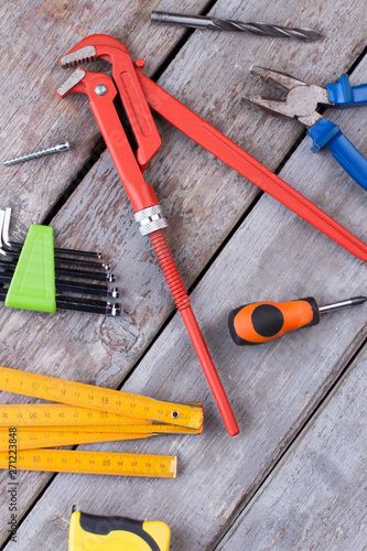 Poster Pays d Europe Tools for repair and construction. Screwdriver, pipe wrench pliers, measuring tape, folding ruler, drill bit and screw on wooden background.