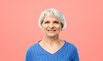 old people concept - portrait of smiling senior woman in blue sweater over pink or living coral background