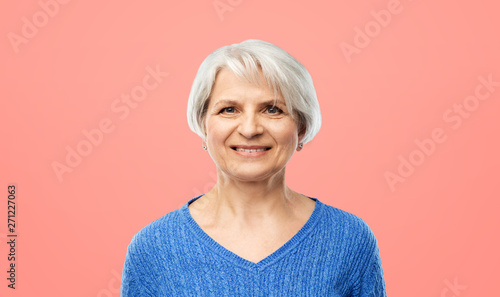 obraz dibond old people concept - portrait of smiling senior woman in blue sweater over pink or living coral background