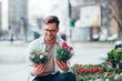 Smiling young man holding two potted plants outdoors, buying flowers.