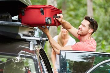 FototapetaMann packt Koffer in die Dachbox auf dem Auto