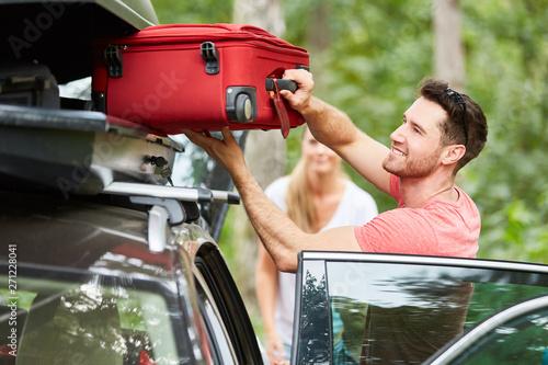 obraz PCV Mann packt Koffer in die Dachbox auf dem Auto