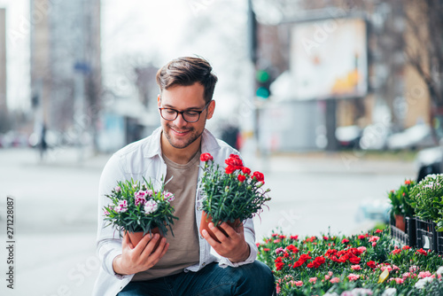Smiling young man holding two potted plants outdoors, buying flowers Canvas Print