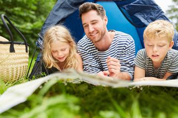 Vater und zwei Kinder im Zelt beim Camping