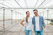 Leinwanddruck Bild - Portrait of a young couple of successful farmers at modern greenhouse.
