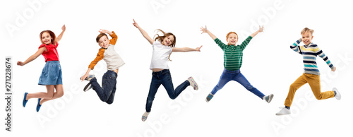 Photo childhood, fun and motion concept - happy children jumping over white background