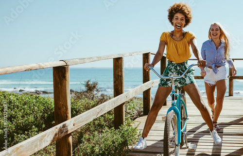 Girls having fun with bike on boardwalk Poster Mural XXL