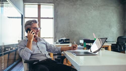 Fototapeta Businessman in office talking on phone obraz