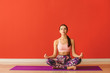 canvas print picture - Sporty woman practicing yoga near color wall