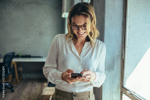 Businesswoman using her smart phone in office