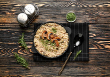 Frying Pan With Tasty Risotto On Wooden Table